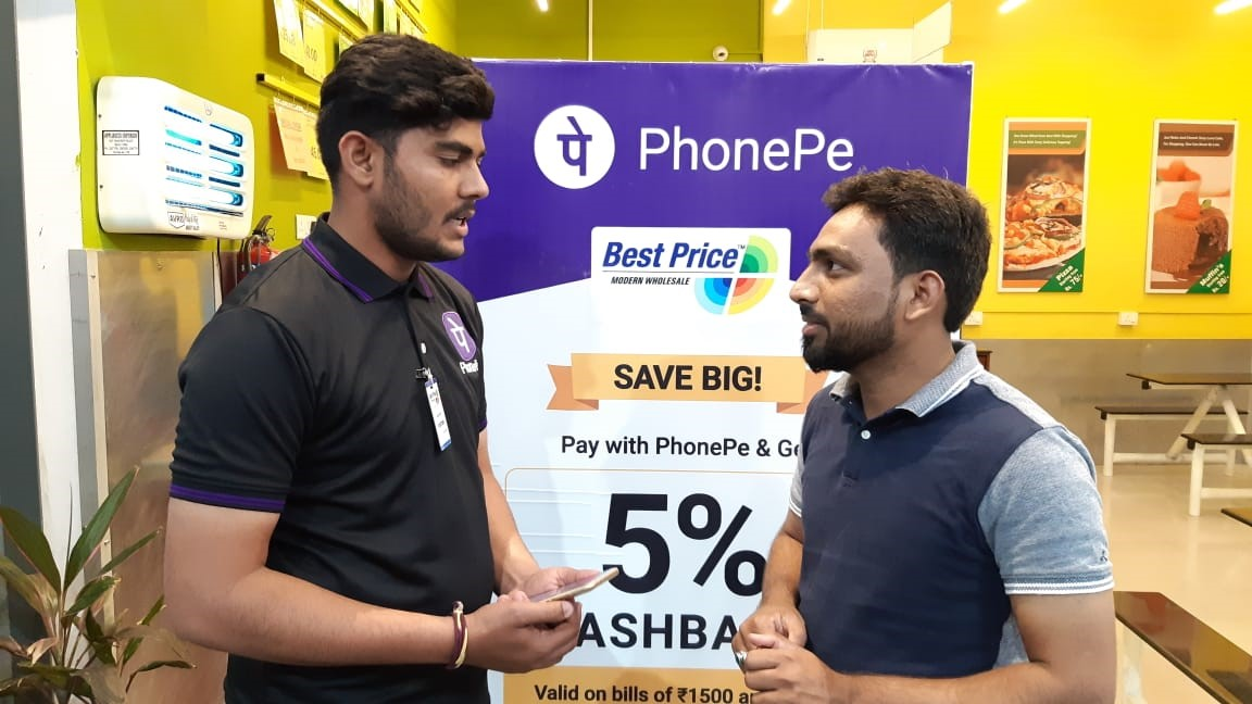An employee assists a customer at a PhonePe station