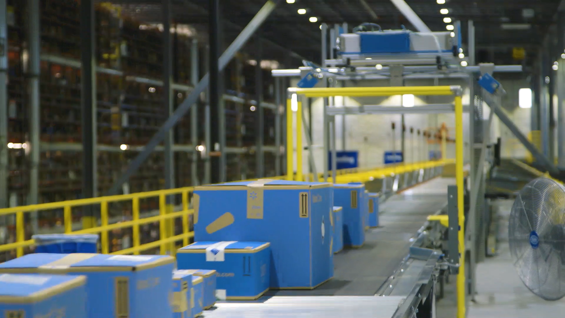 Blue boxes move on a belt in a Walmart fulfilment center