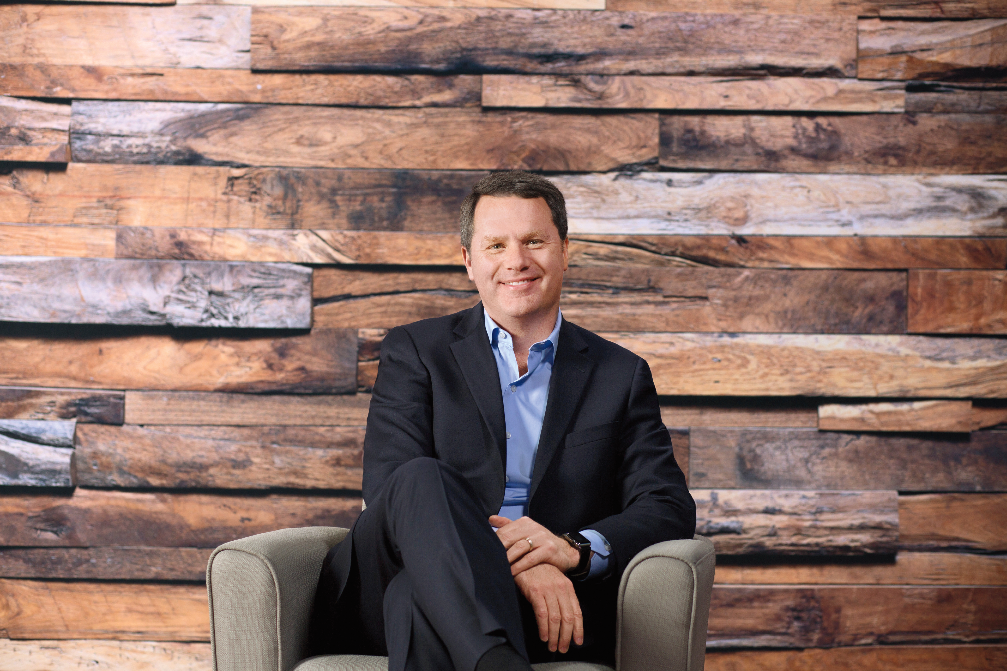 Doug McMillon sitting in front of wood wall