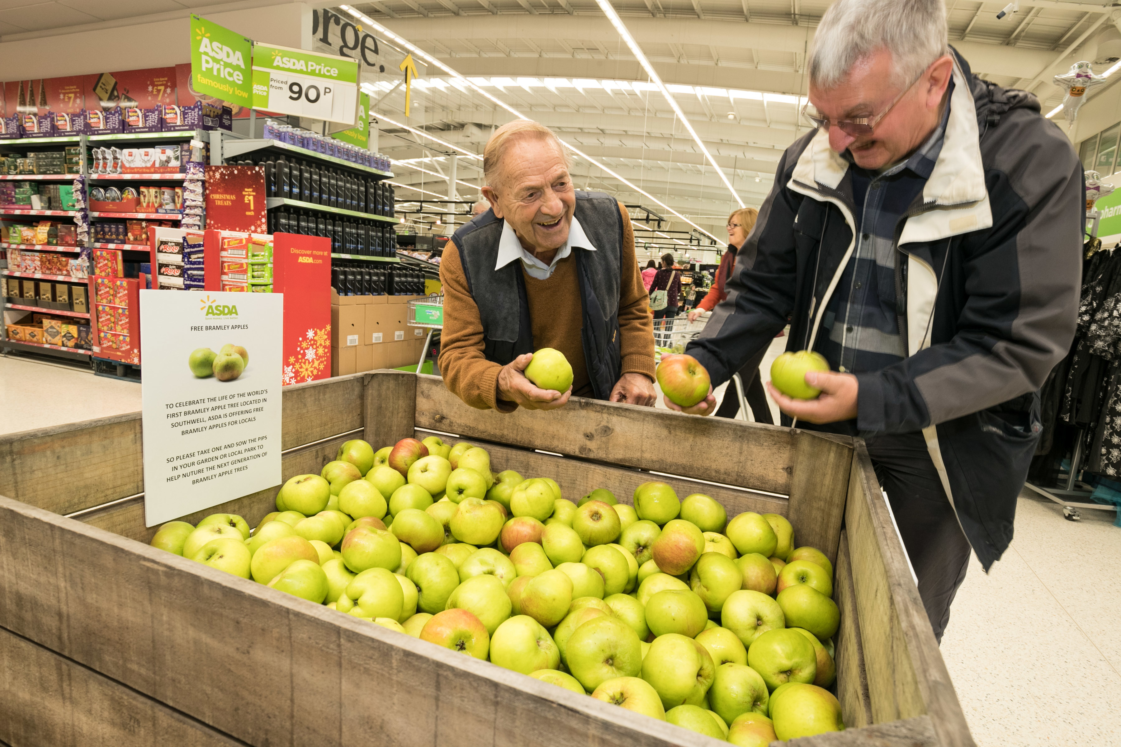 Customers pick up a free Bramley apple from Asda West Bridgford