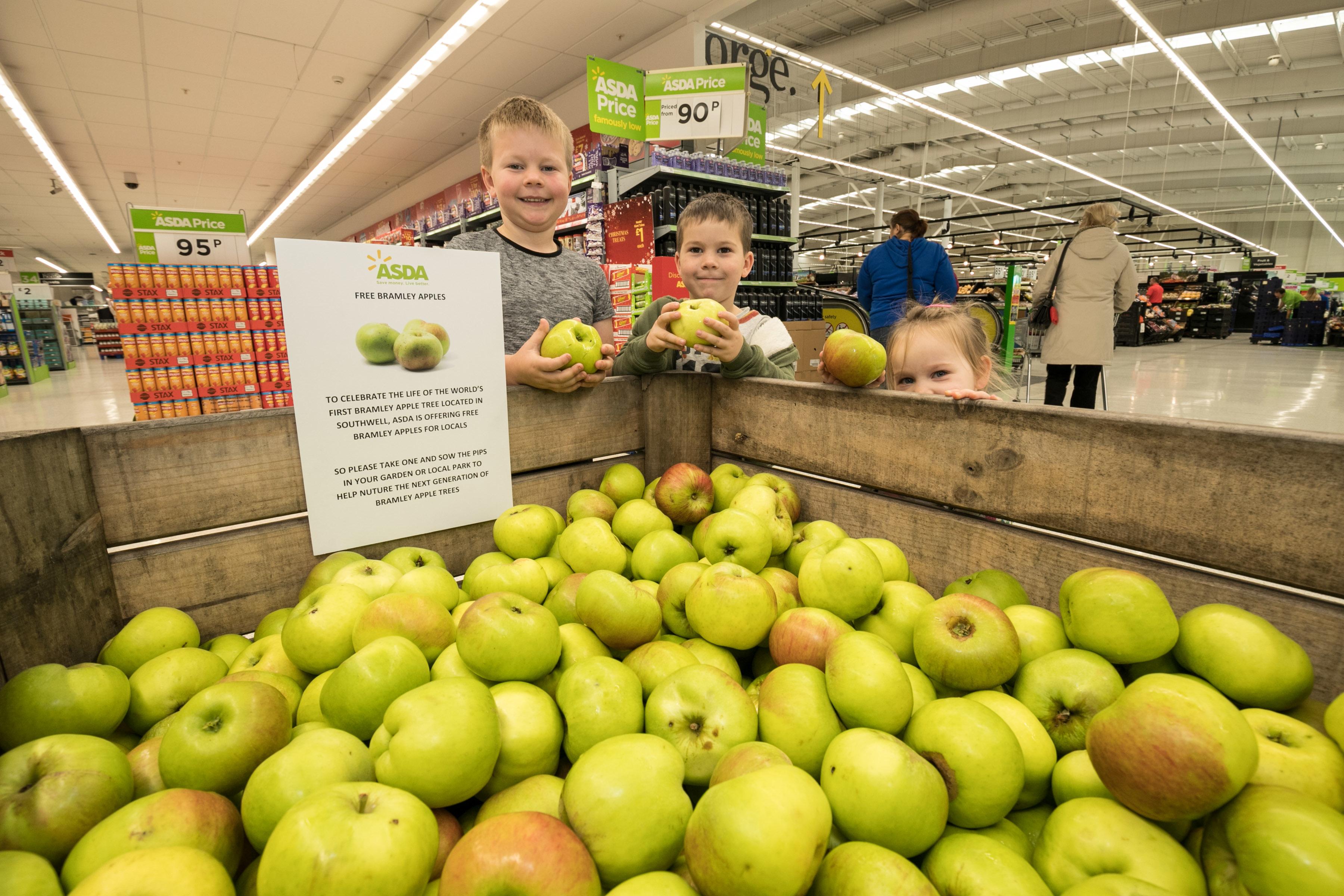 Children pick up a free Bramley apple from Asda West Bridgford