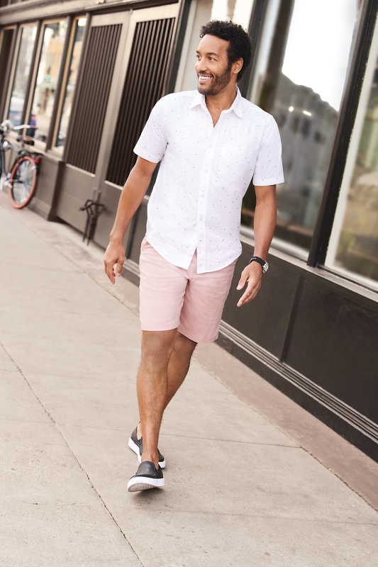 A man walks down a street in a white shirt and pink shorts