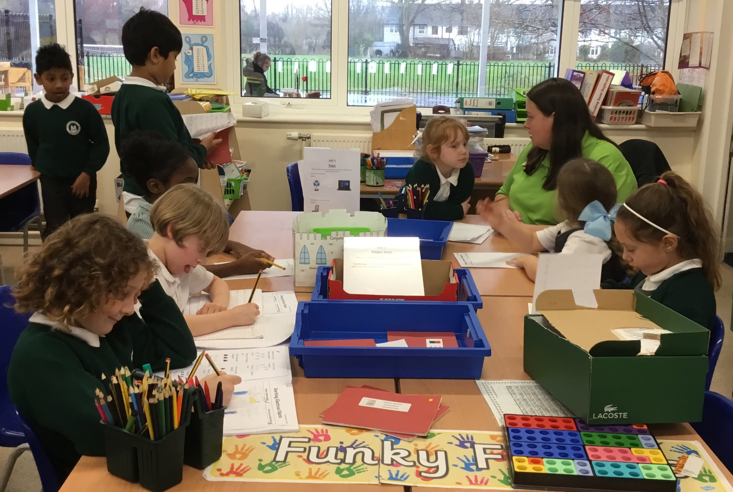 Asda Romford community champion Liz Brown helping pupils at Mead Primary School