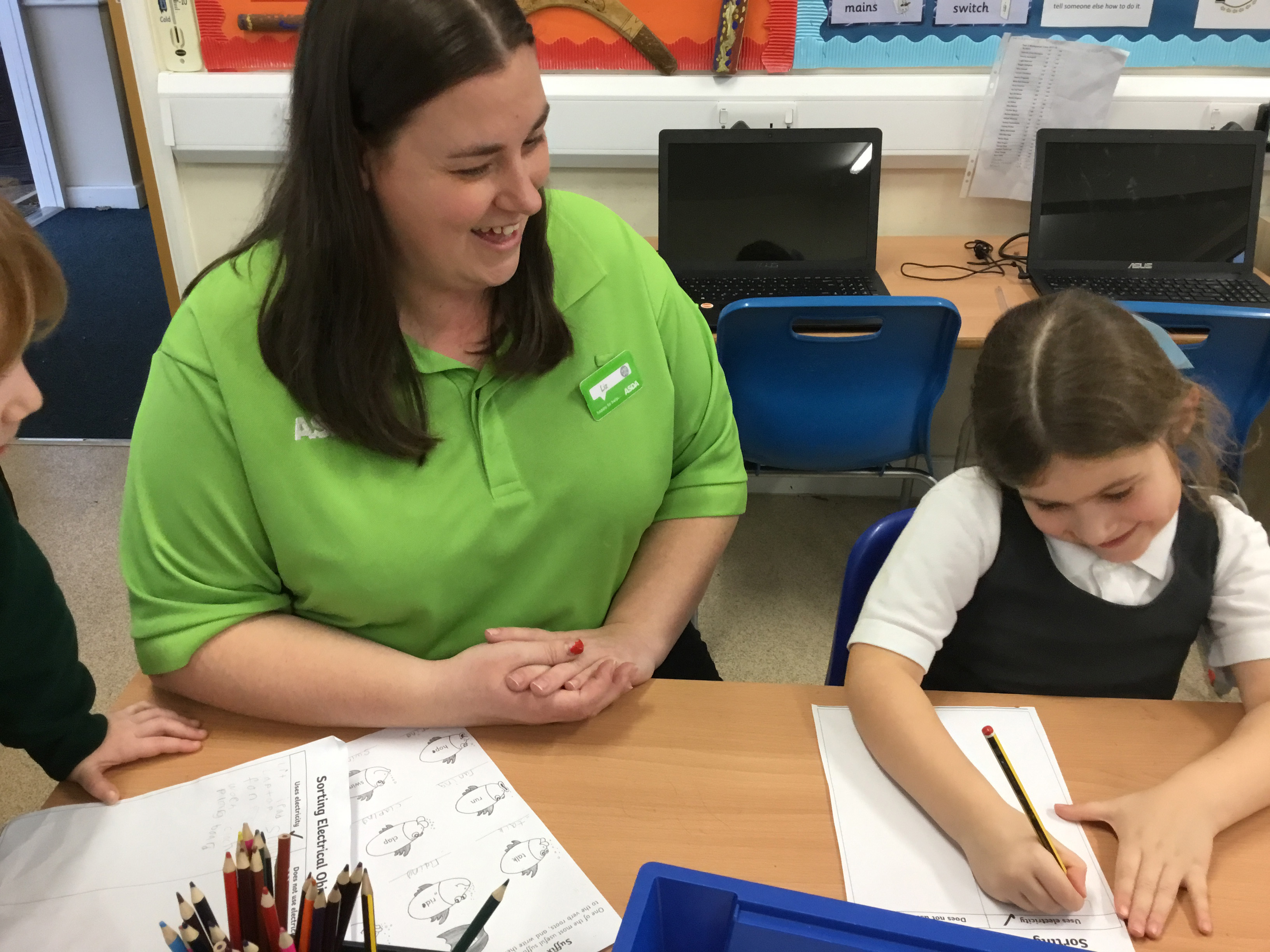 Asda Romford community champion Liz  Brown helps a pupil