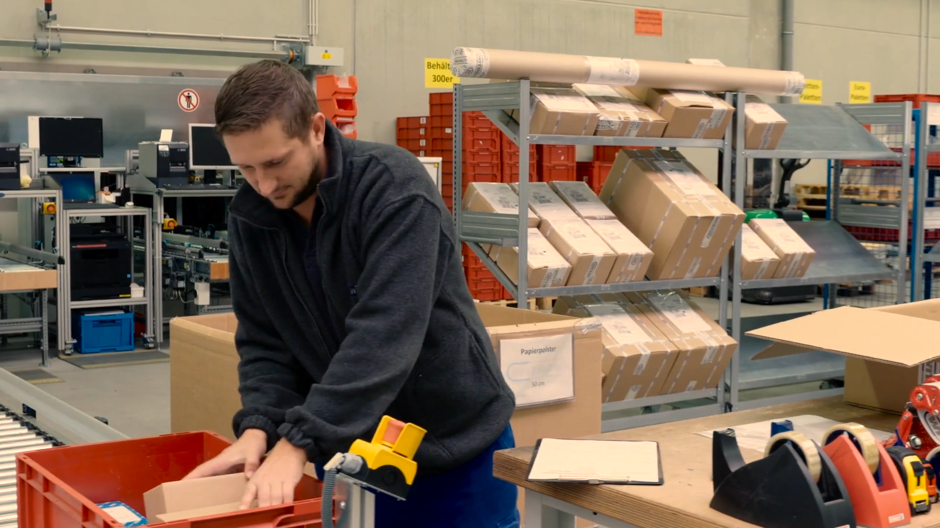 A man packs products at a high-tech distribution center