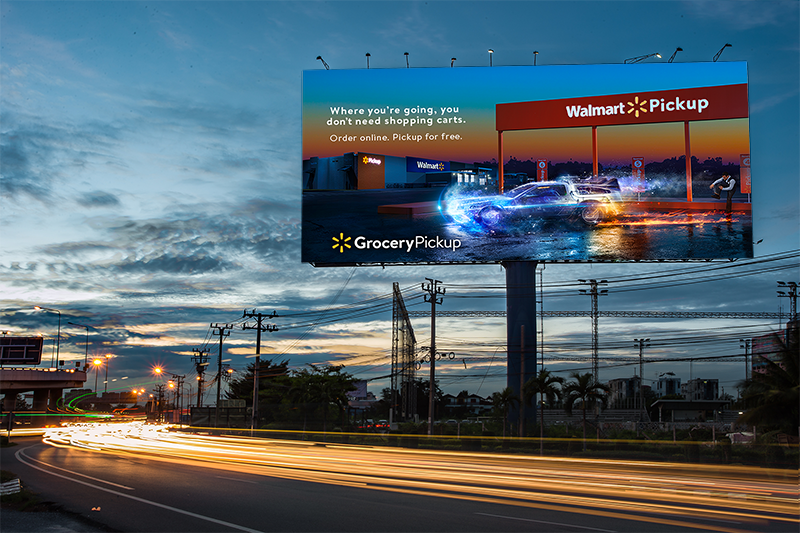 Cars speeding on a highway passed a billboard promoting Walmart's online grocery pickup