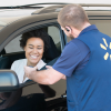 Associate standing outside of car helping customer with grocery pickup
