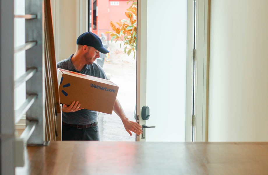 A man is delivering shipping boxes inside a customer's home