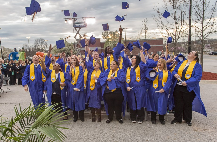 A group of associates toss their graduation caps in the air