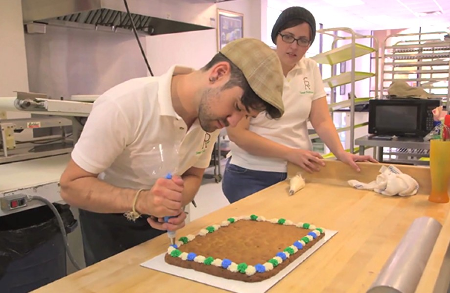 Stephen Robichaux pipes icing on a cake while wife, Jennifer, looks on from the side