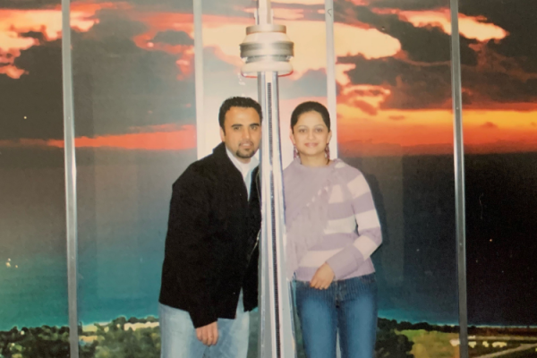 Shahpoor Amiri and his wife, Zainab Amiri, pose beside a CN Tower model in Toronto in the 2000s.