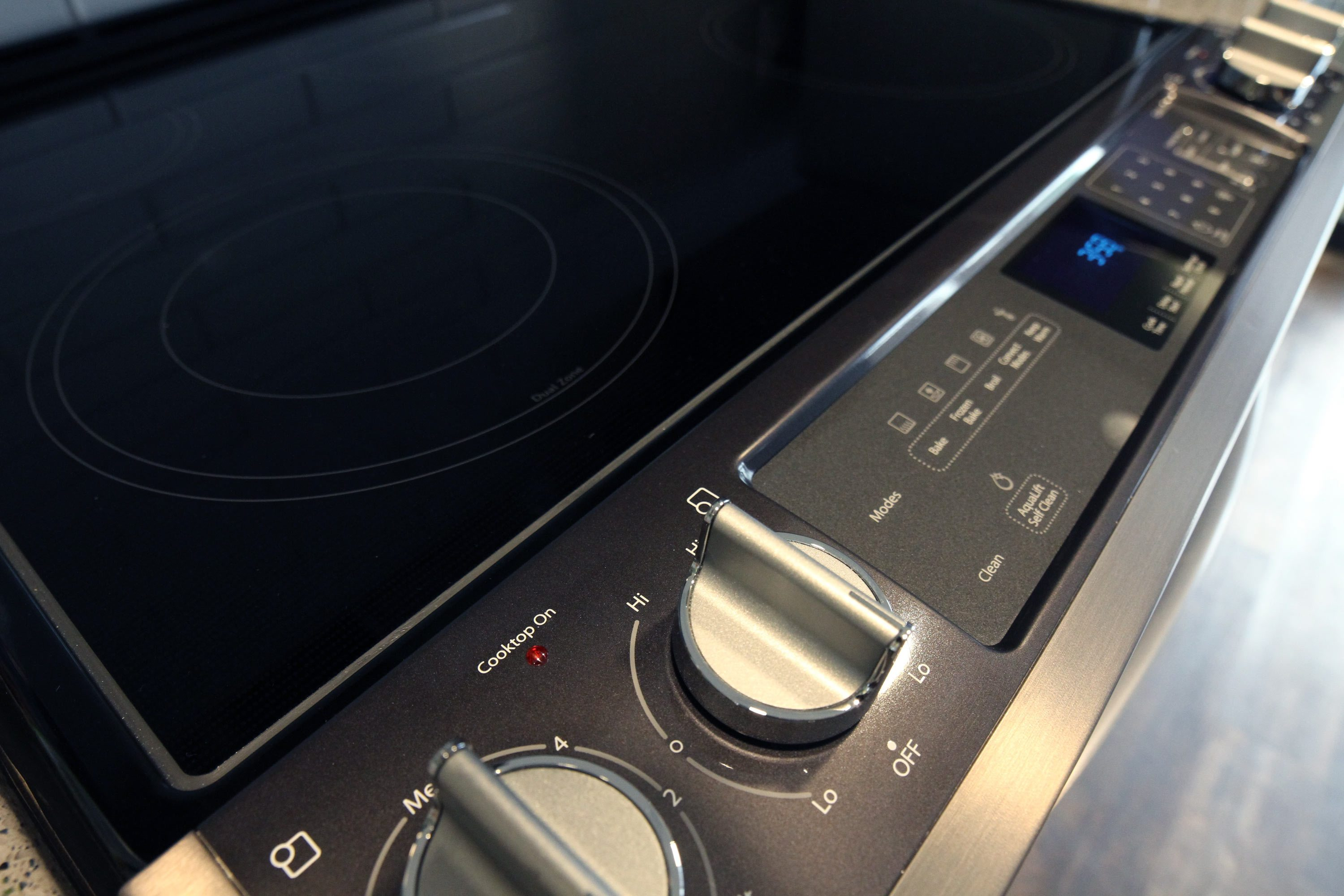 A close up image of a black stove cook top with stainless steel knobs