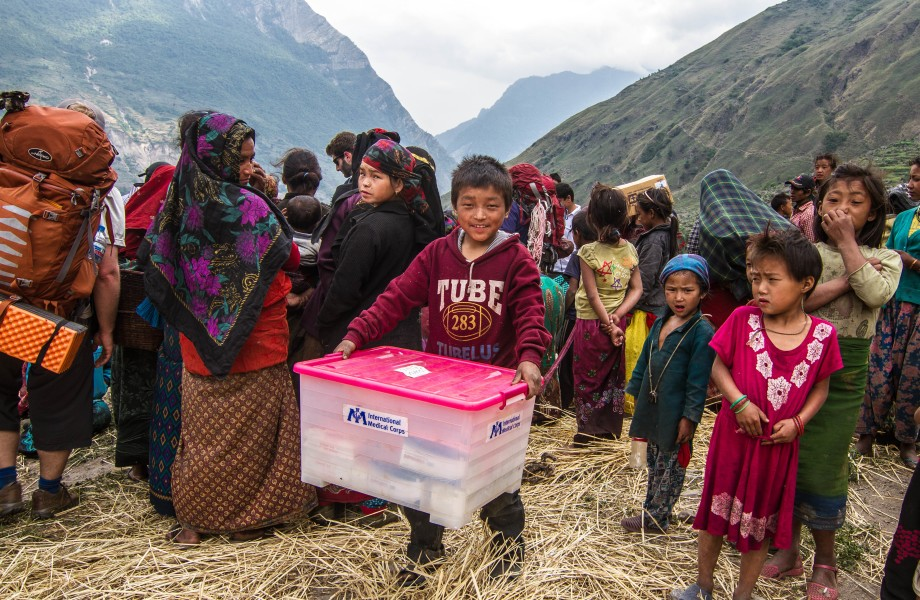 A group of children and women are in a mountainous area with one plastic box of supplies