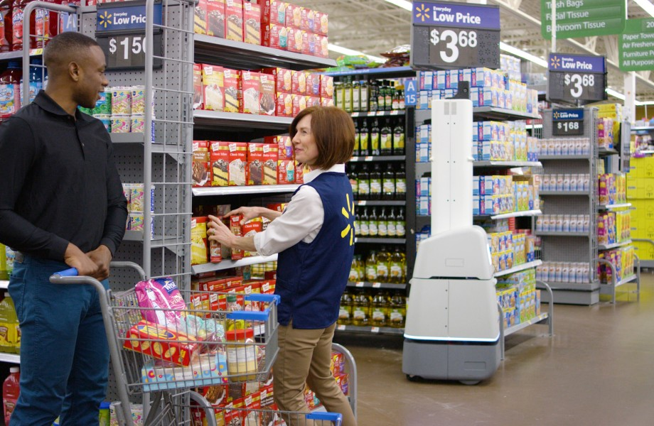 Associate helps a customer as an Autonomous Shelf Scanner works in the background