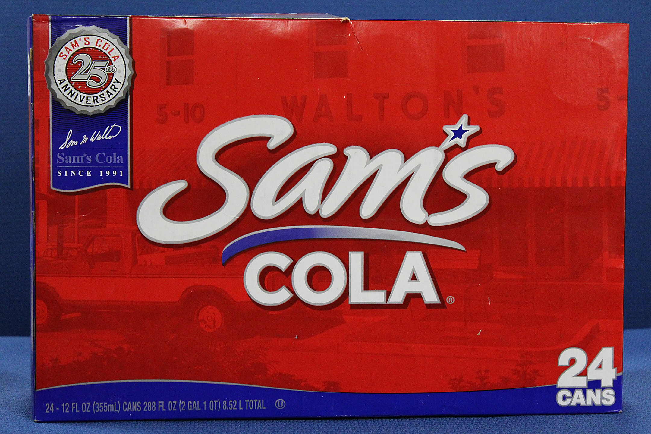 "A red cardboard box with ""Sam's Cola"" written on the side is holding cans of soda"