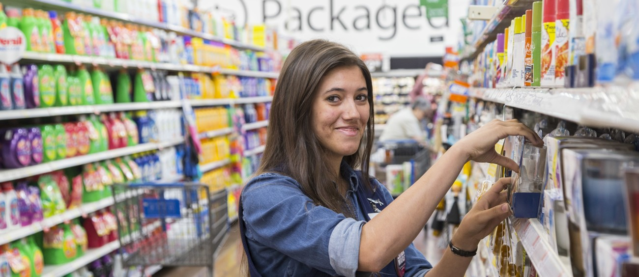 A female associate stocks a shelf in the laundry detergent aisle