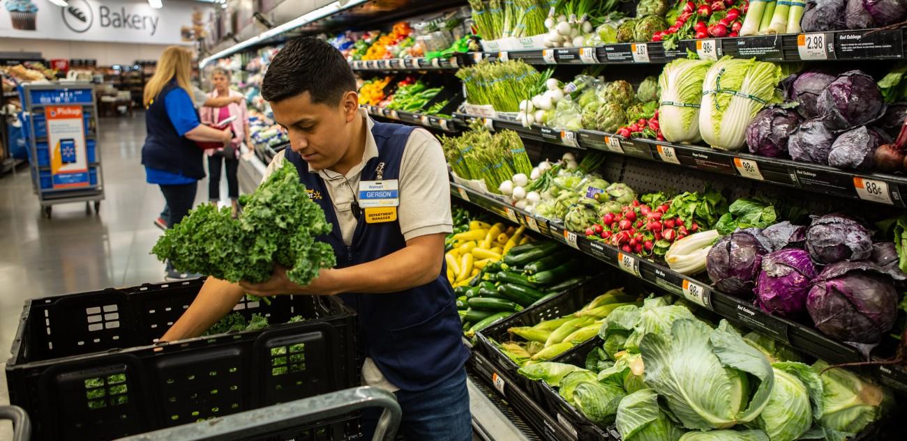 An associate stocks lettuce and fresh produce