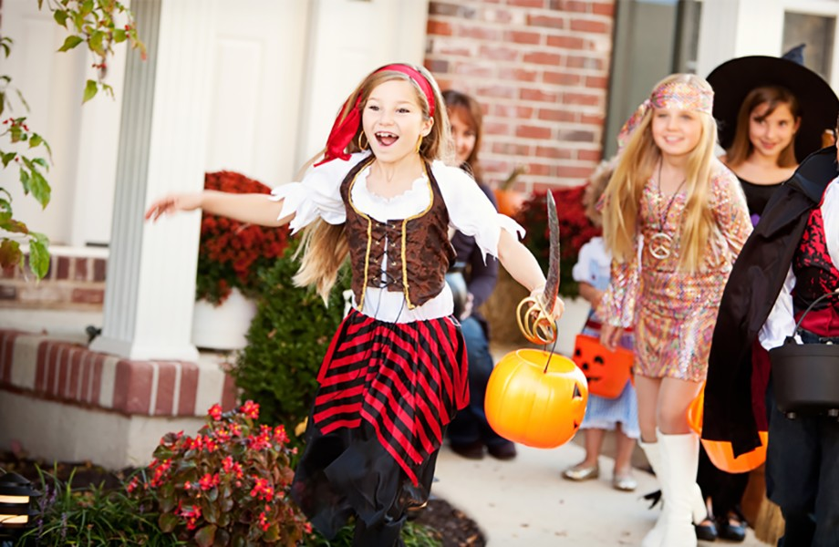 A group of kids in Halloween costumes leave a house after trick-or-treating