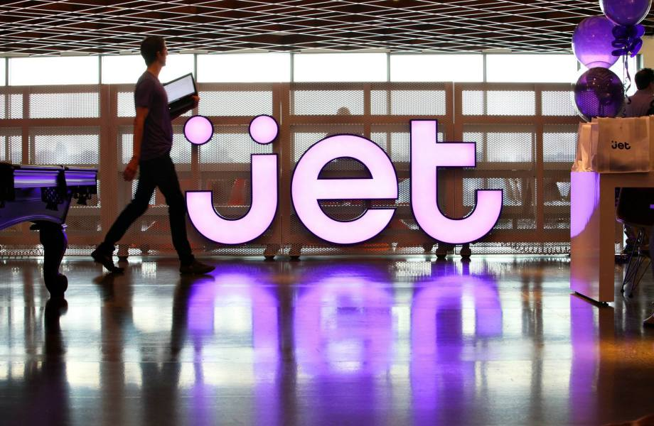 A Jet.com associate walks through a lobby with a large illuminated Jet logo behind him