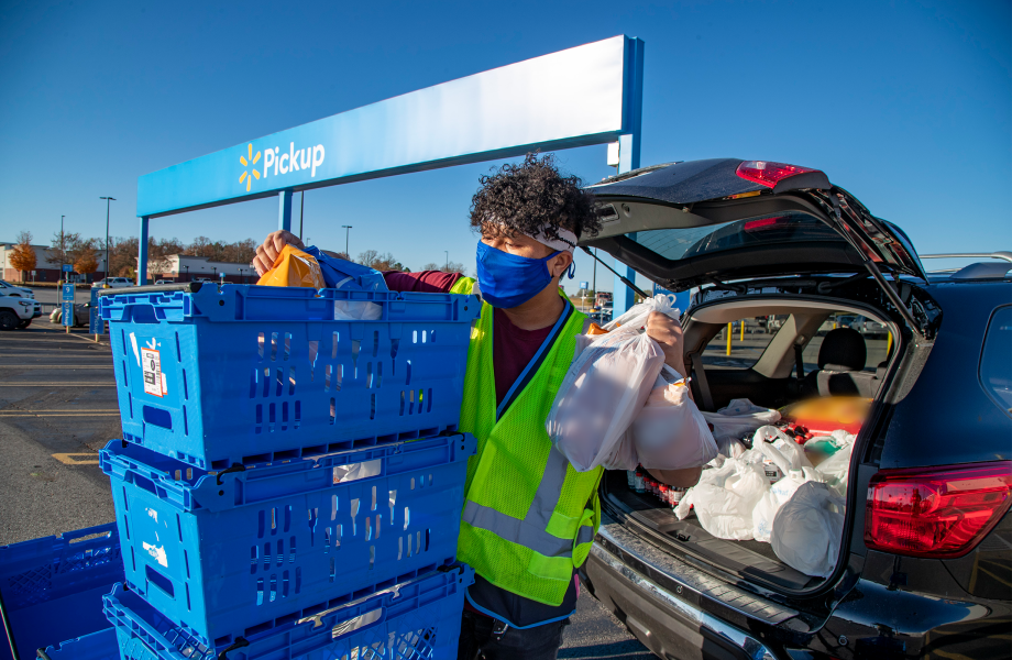 A masked associate places a pickup order in a vehicle