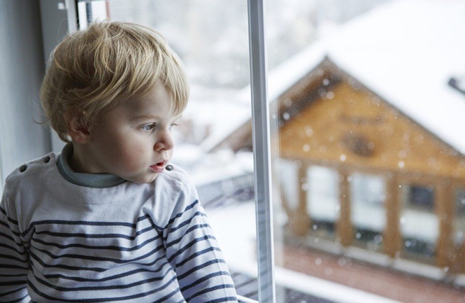A young boy watches the snow fall outside through the window