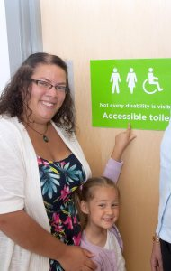 """Two woman and a young girl stand near a sign that reads """"not all disabilities are visible"""""""