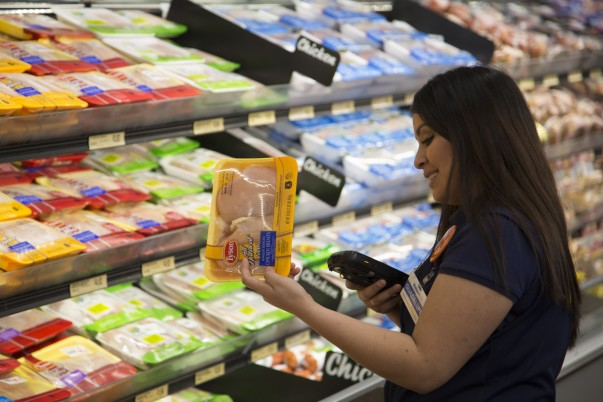 A female associate scans chicken breasts for grocery pickup