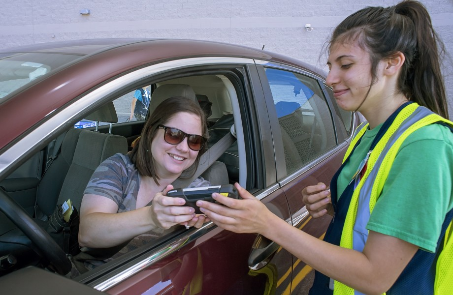 An associate helps a customer sign for a grocery pickup order