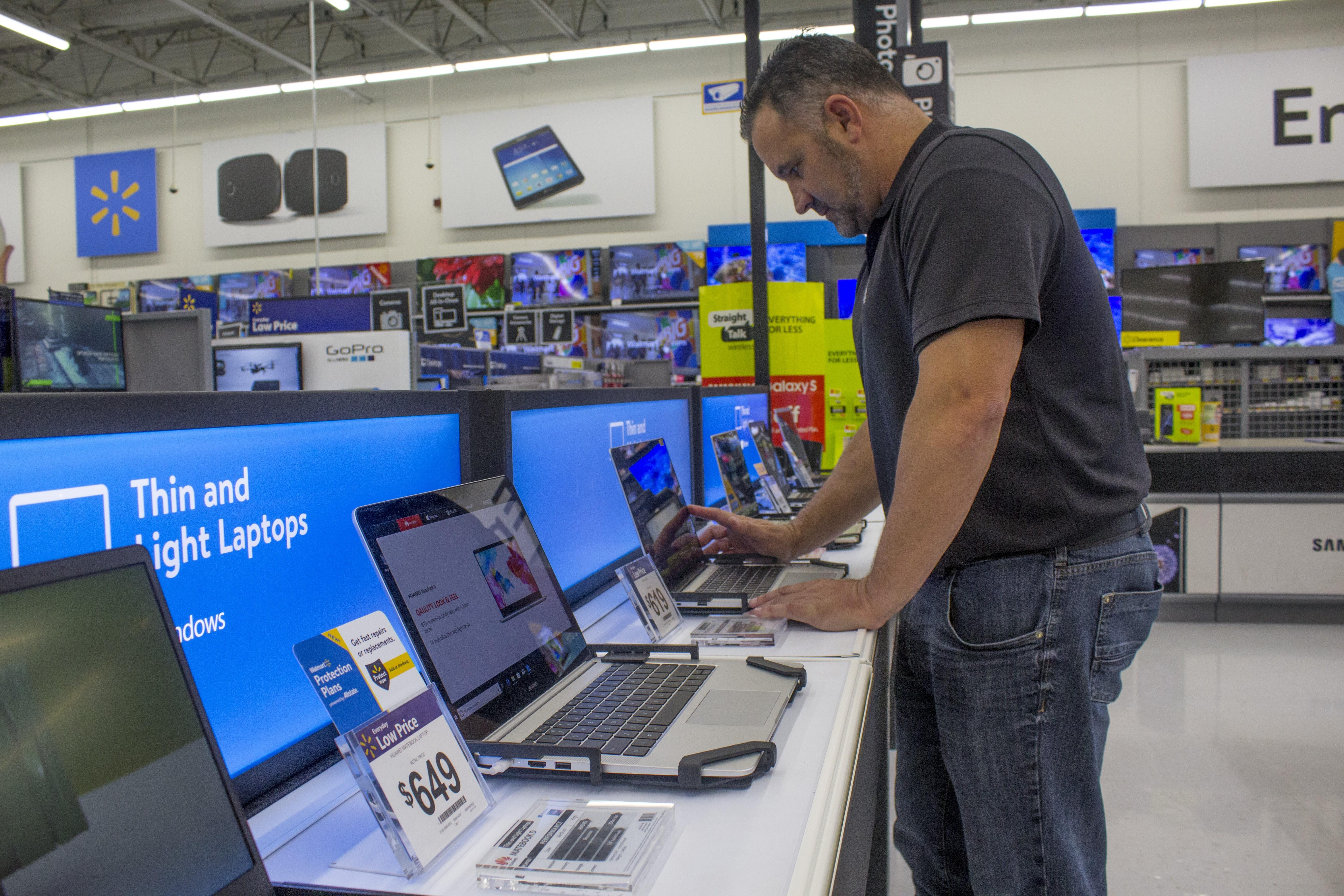 A customer shops for a laptop in a Walmart Supercenter