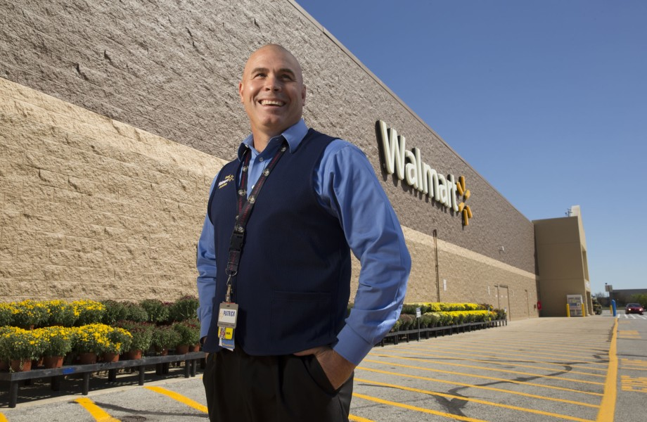 A man wearing a Walmart vest is standing outside of a Walmart store