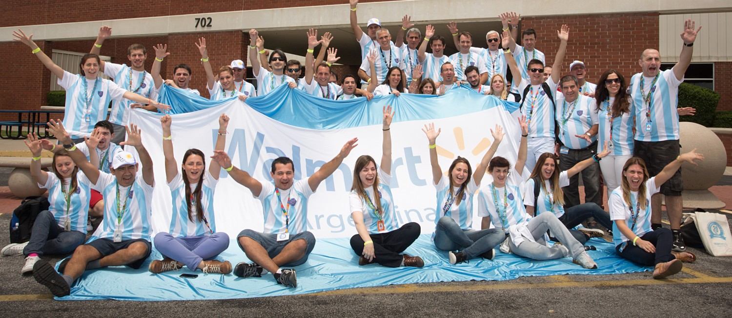 "A group of associates smile and lift their arms up while gathered around a large light blue and white banner which reads ""Walmart Argentina""."