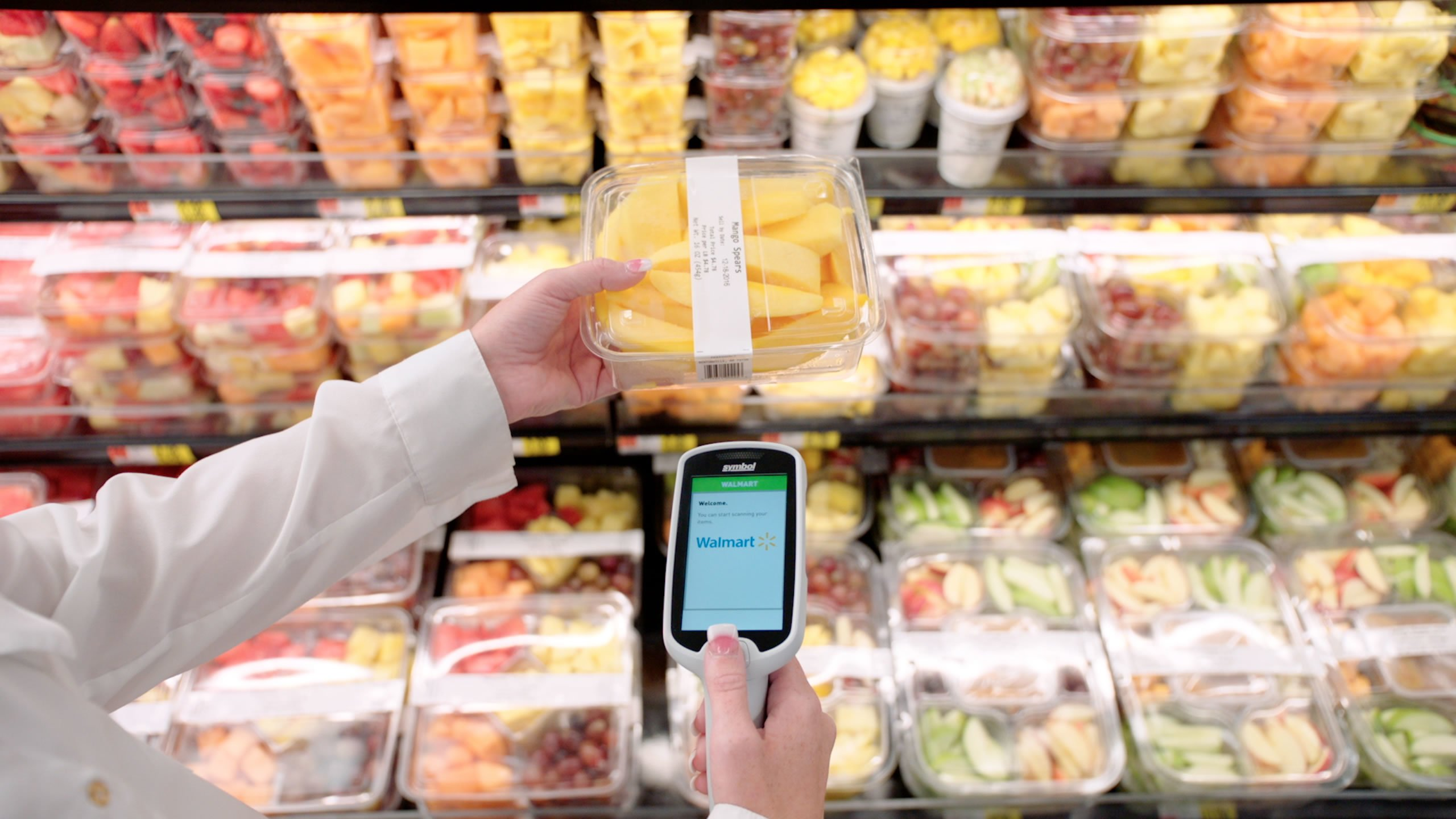 A customer uses a Scan & Go handheld device to scan fresh mango produce