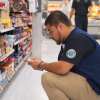An associate uses their phone to check product availability