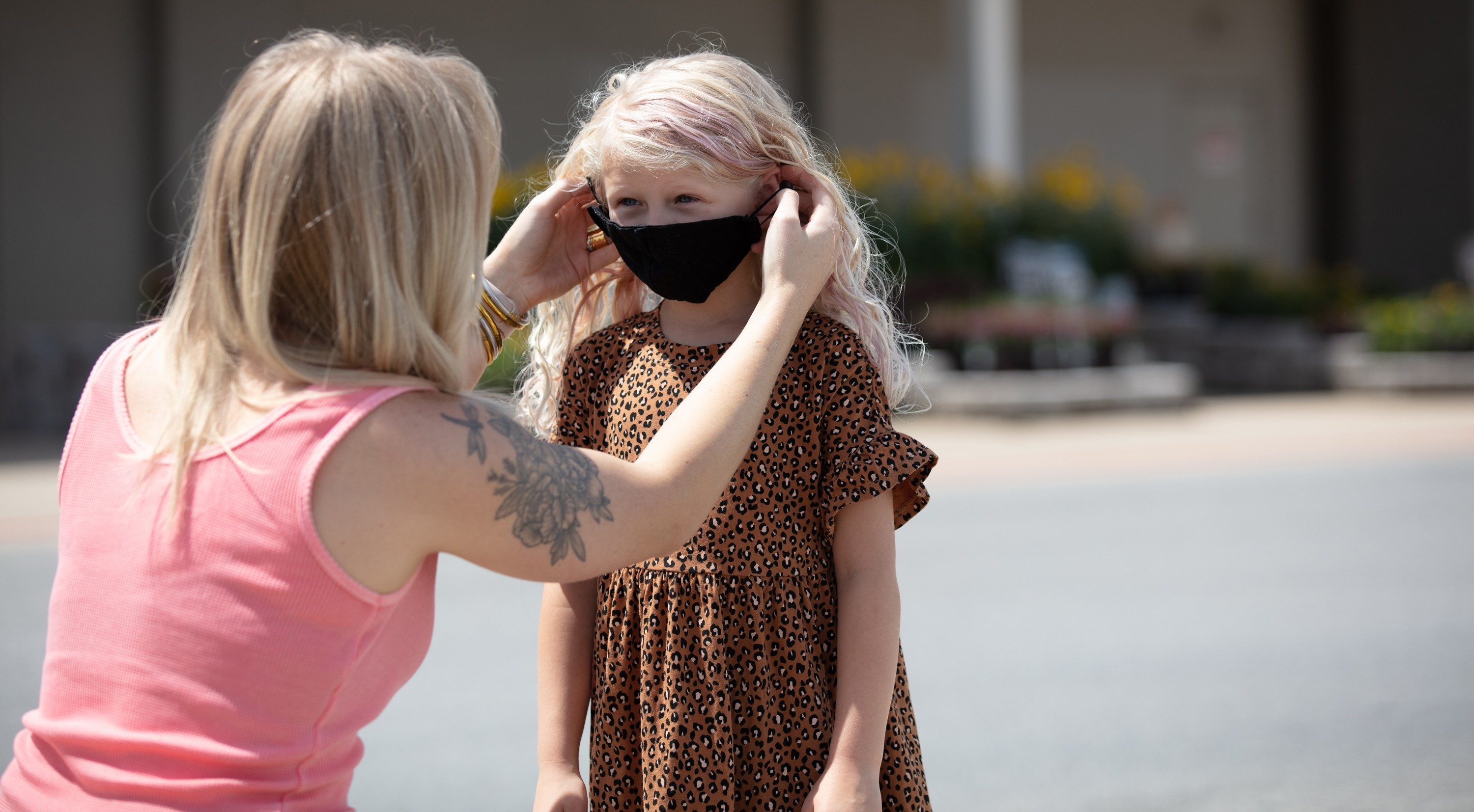 Calley Williams, a Walmart customer, puts a mask on her daughter