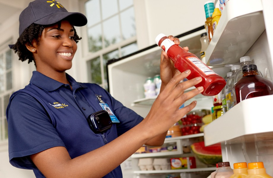 Associate stocking a customer's fridge in garage with InHome Delivery - Crop