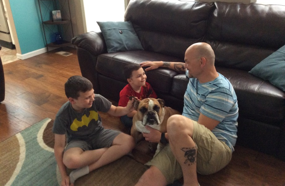A father and his two sons pet their family dog while sitting on the floor of their living room