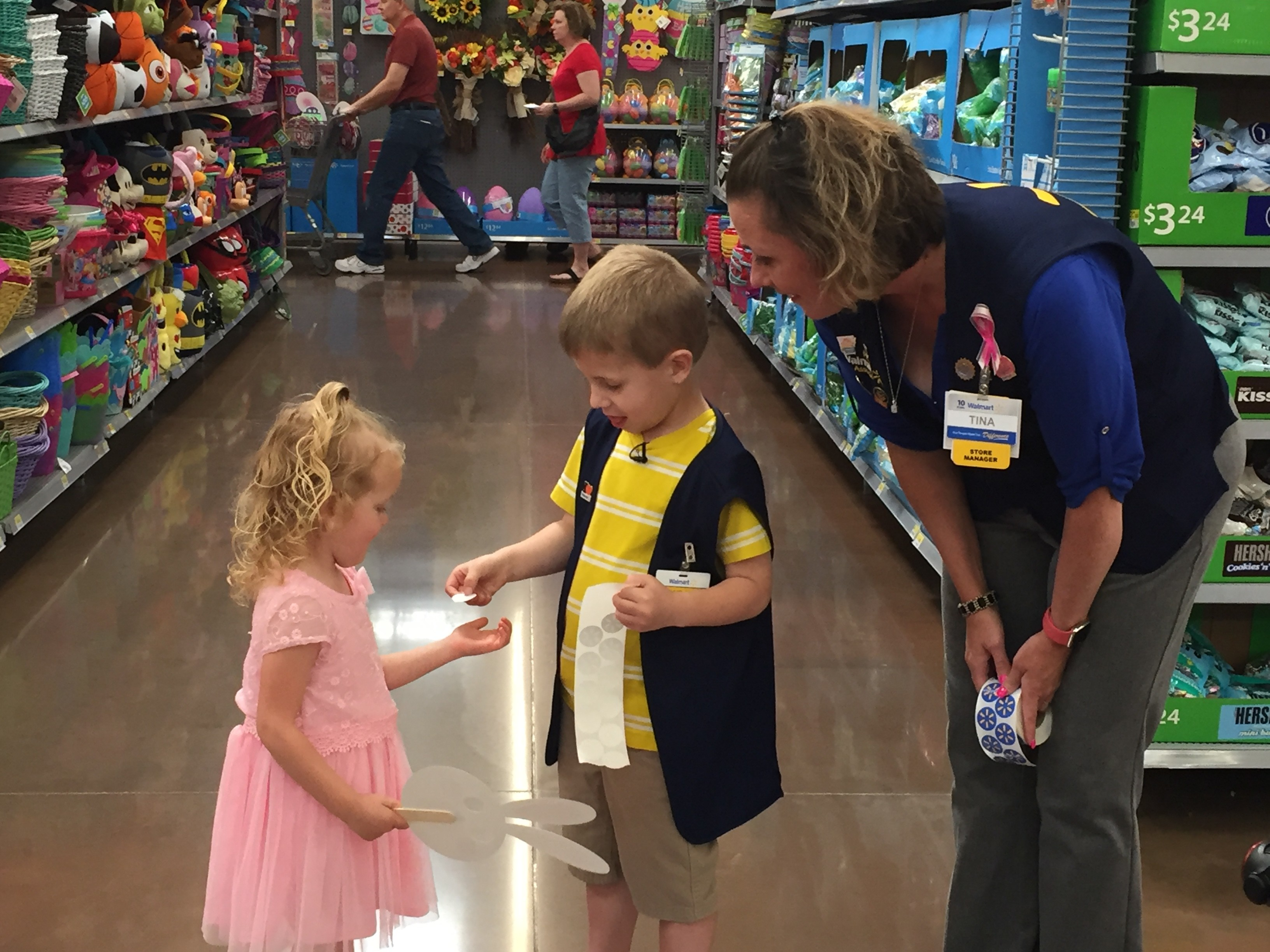 A young boy dressed as an associate for a day helps another young customer