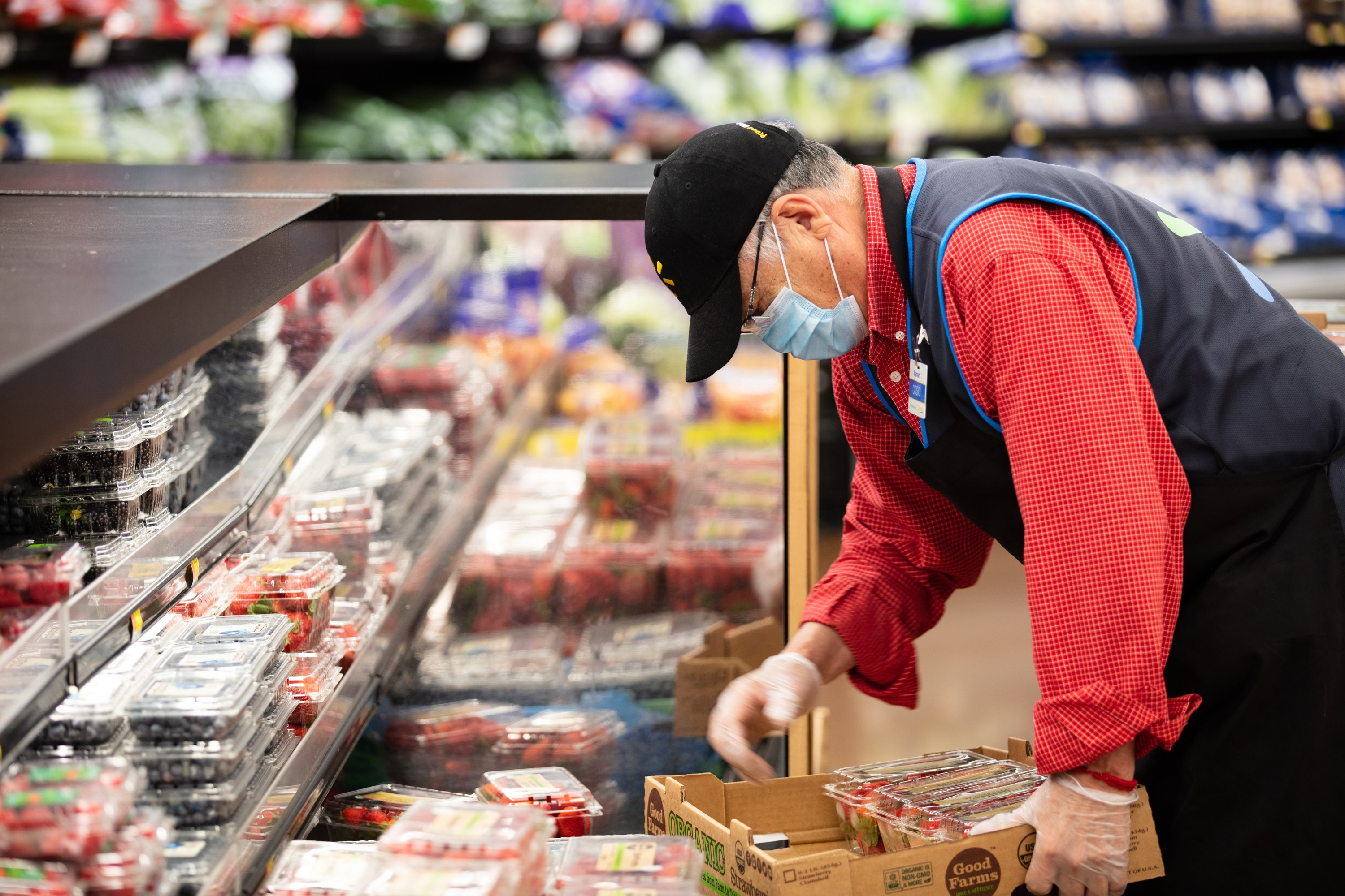 An associate wears a mask while stocking strawberries