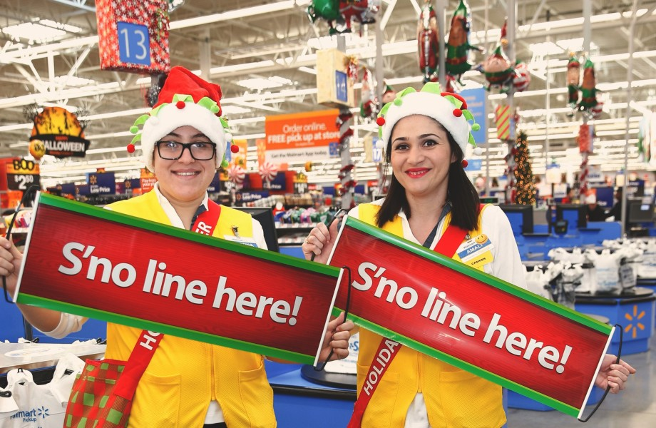 Two Holiday Helpers holding up S'no line here! signs