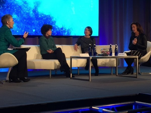 Kathleen McLaughlin speaks with a panel of others on stage during the International Women's Forum