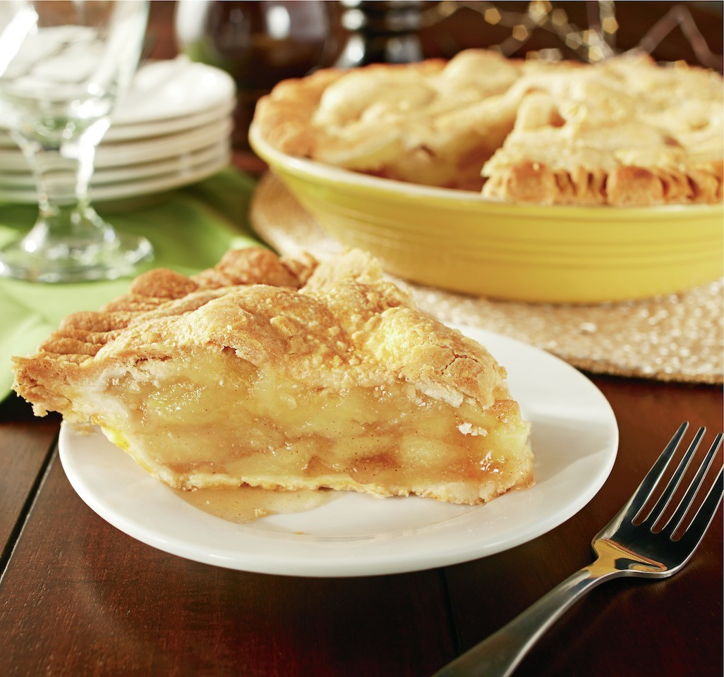 A large slice of baked apple pie sits on a plate in front of the whole pie