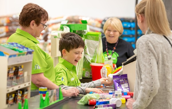 Colleagues at Asda Falkirk show Aaron how to work a checkout
