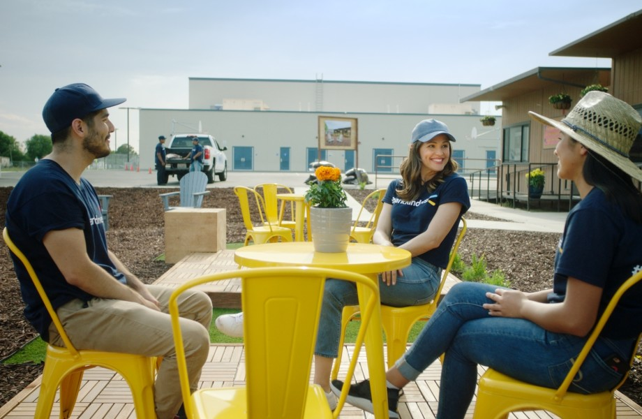 Jennifer Garner chats with two Walmart Associates outside at a small yellow table