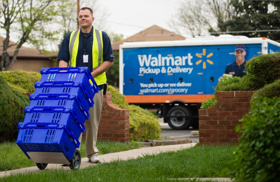 A man is pushing a dolly that has several crates filled with groceries on it