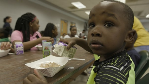 A child pours milk on cereal at the G.W. Henderson Community Center in Tunica, Mississippi