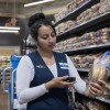 An associate uses a mobile device to scan a package of buns