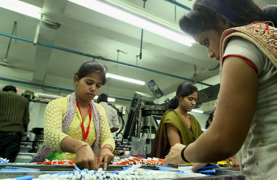 Women dressed in saris put together pens on assembly line in factory