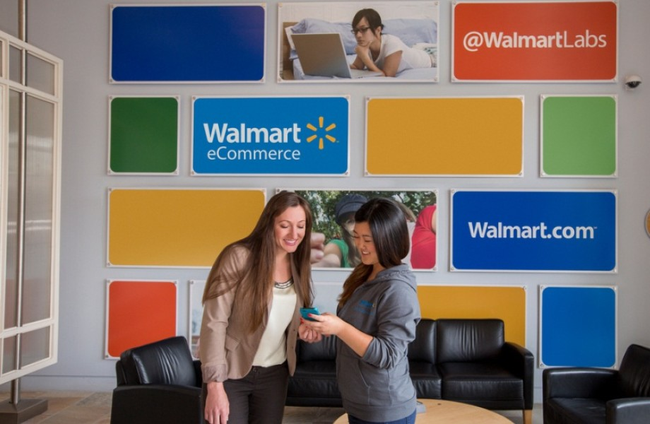 Two Walmart Labs Associates look at a cell phone