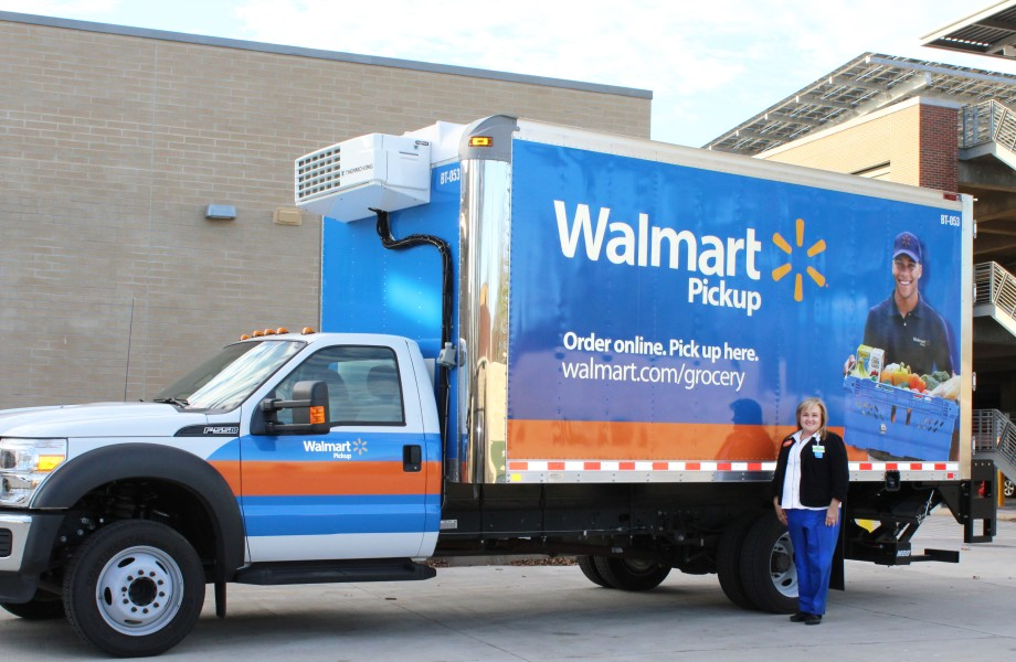 Ellen Martinez stands by a blue Walmart Pickup Grocery boxtruck