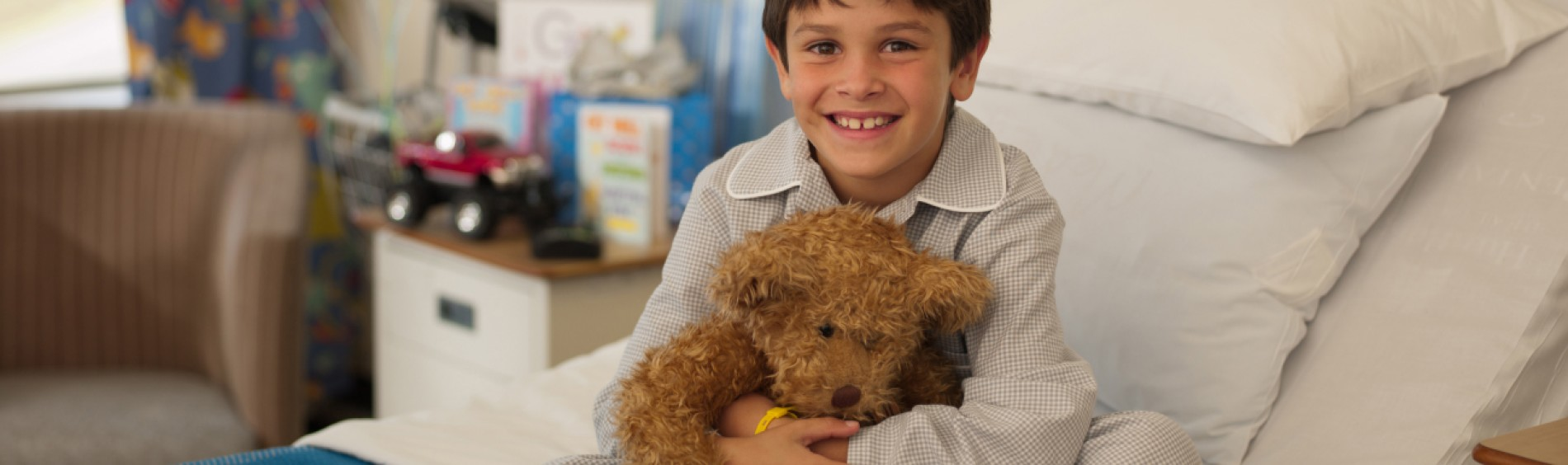 A boy in pyjamas smiles and hugs a teddy bear while sitting in a hospital room